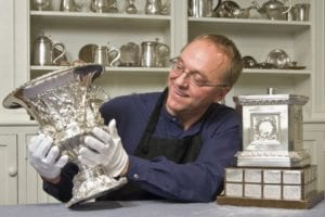 conservator examines silver trophy