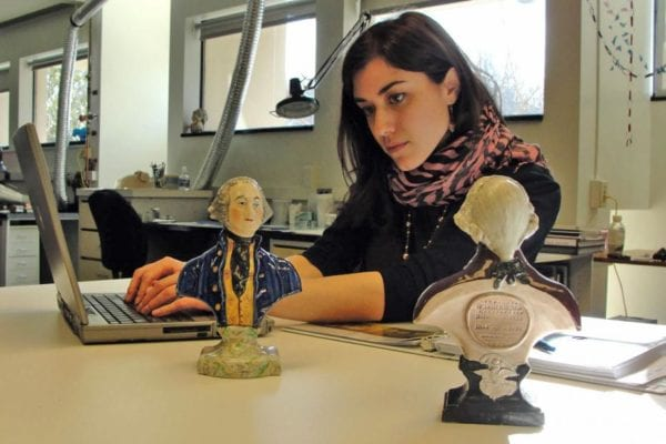 Lauren Fair surveying Staffordshire busts of George Washington