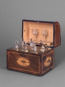 Liquor chest, various case bottles, tray, and wineglasses.