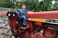 Young boy pretending to drive a tractor at Truck and Tractor Day
