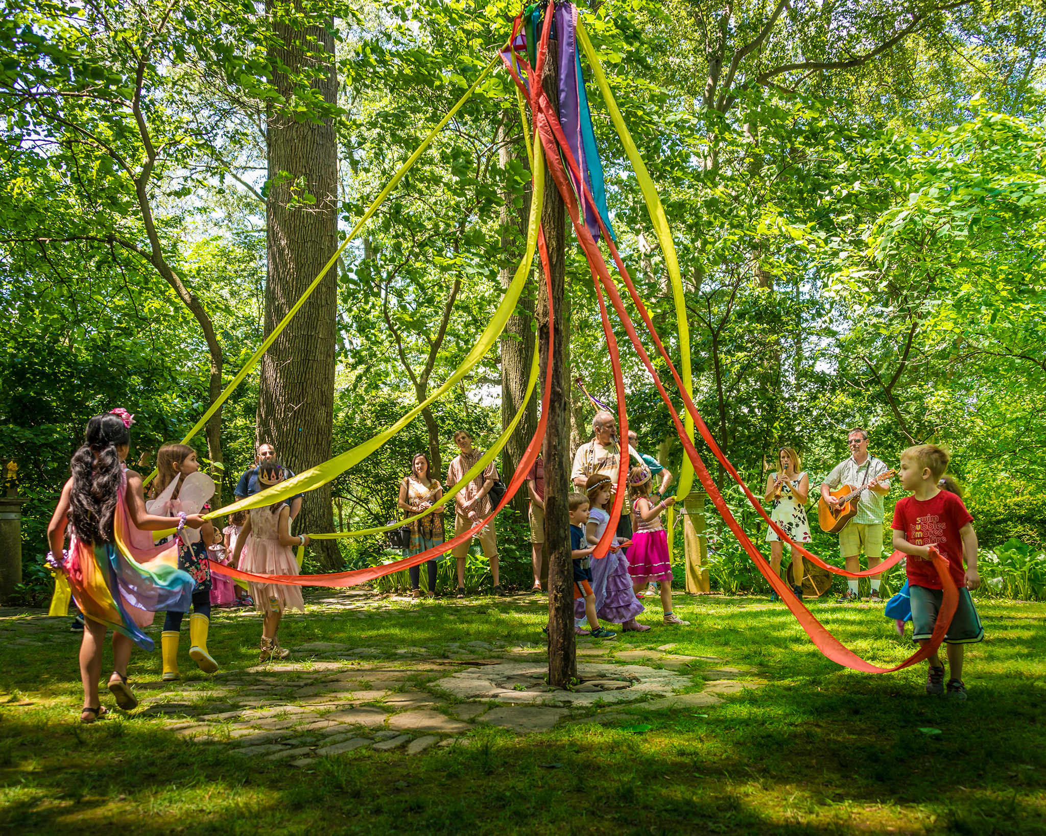Children dancing around a maypole in the Enchanted Woods.