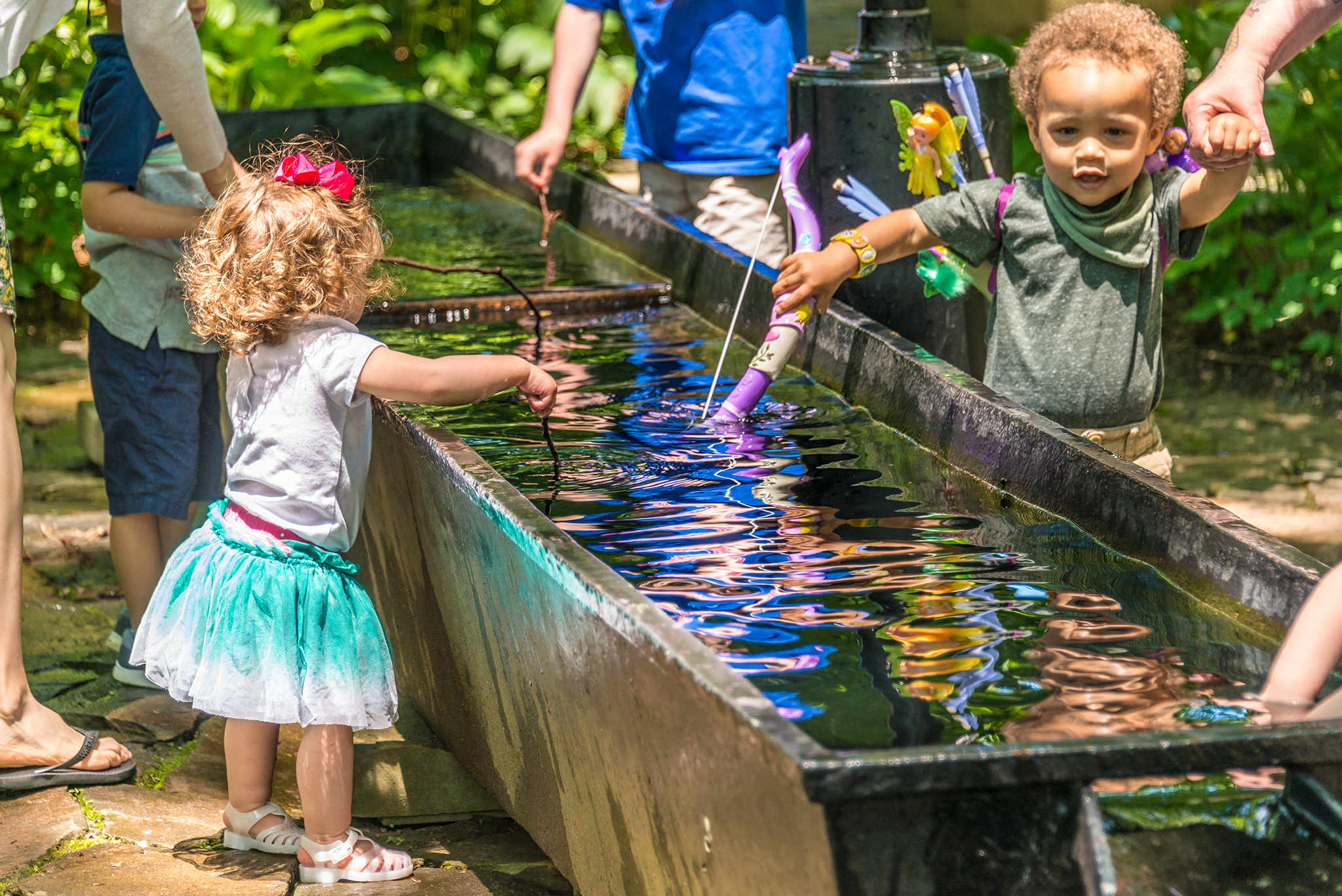 Children playing in a fountain trough in the Enchanted Woods.