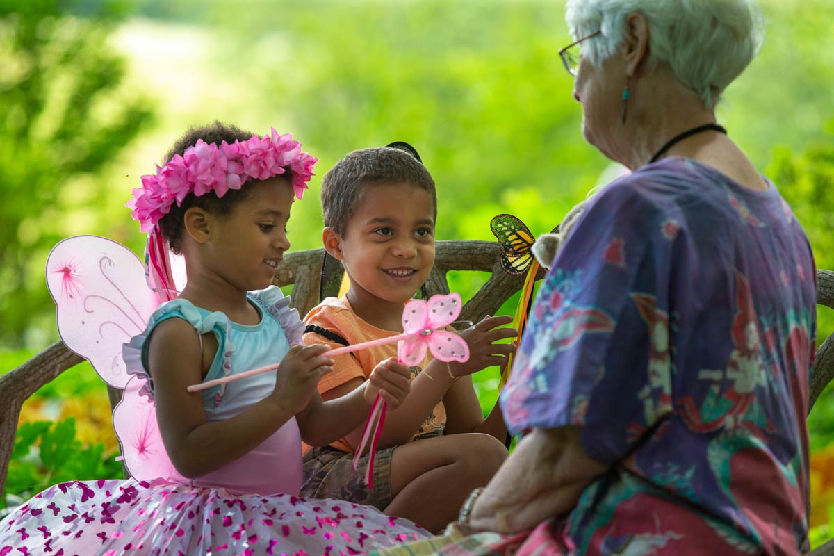 Children dressed as fairies playing with an older woman